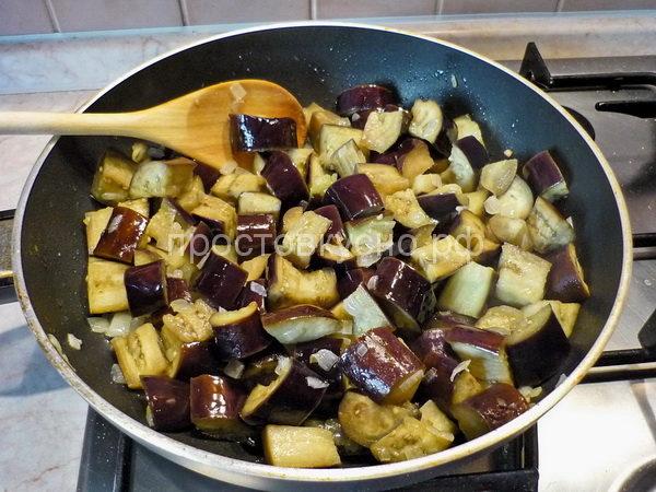 На сковороде разогреть масло. Выложить лук и баклажаны. Помешивая, жарить на среднем огне 5 минут.