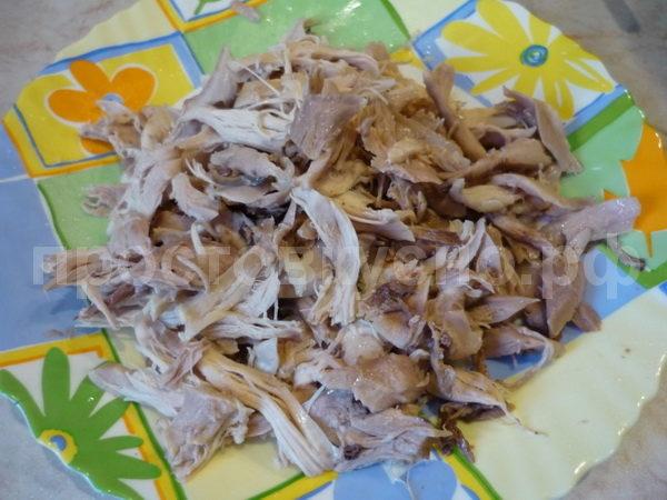 Снимаем с курицы мясо и разделываем его руками на волокна.