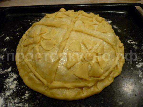 От оставшегося теста отделяем небольшой кусок на украшения, остальное раскатываем в большую лепешку и накрываем начинку будущего пирога. Посередине делаем отверстие для выхода пара. Украшаем на свой вкус остатками теста, смазываем желтком и отправляем в разогретую до 180 градусов духовку на один час.