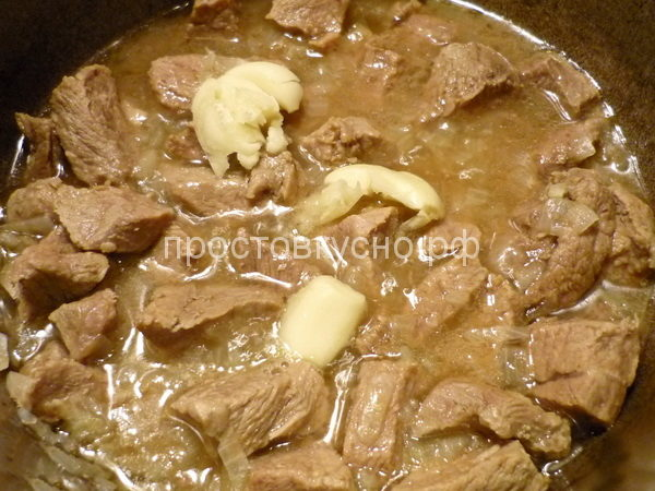 Через 40 минут после начала тушения, добавляем лук в мясо. В процессе тушения лук растворится и перейдет в соус, улучшая его вкус. Не забудьте положить раздавленный чеснок. Все время следим что бы вода полностью не выкипала и по мере необходимости подливаем её.