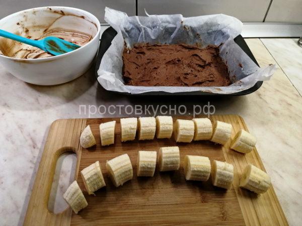Тесто получается довольно густое и плотное. В форму укладываем пергамент, смазываем маслом и выкладываем тесто. Лопаткой или ложкой разравниваем по форме. Бананы чистим и режем на кусочки примерно 3-4 см длиной.